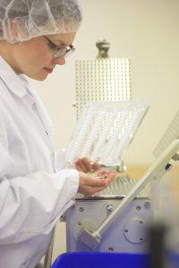 Ellen produserer reinleverkapslene for hånd med en manuell kapselmaskin.