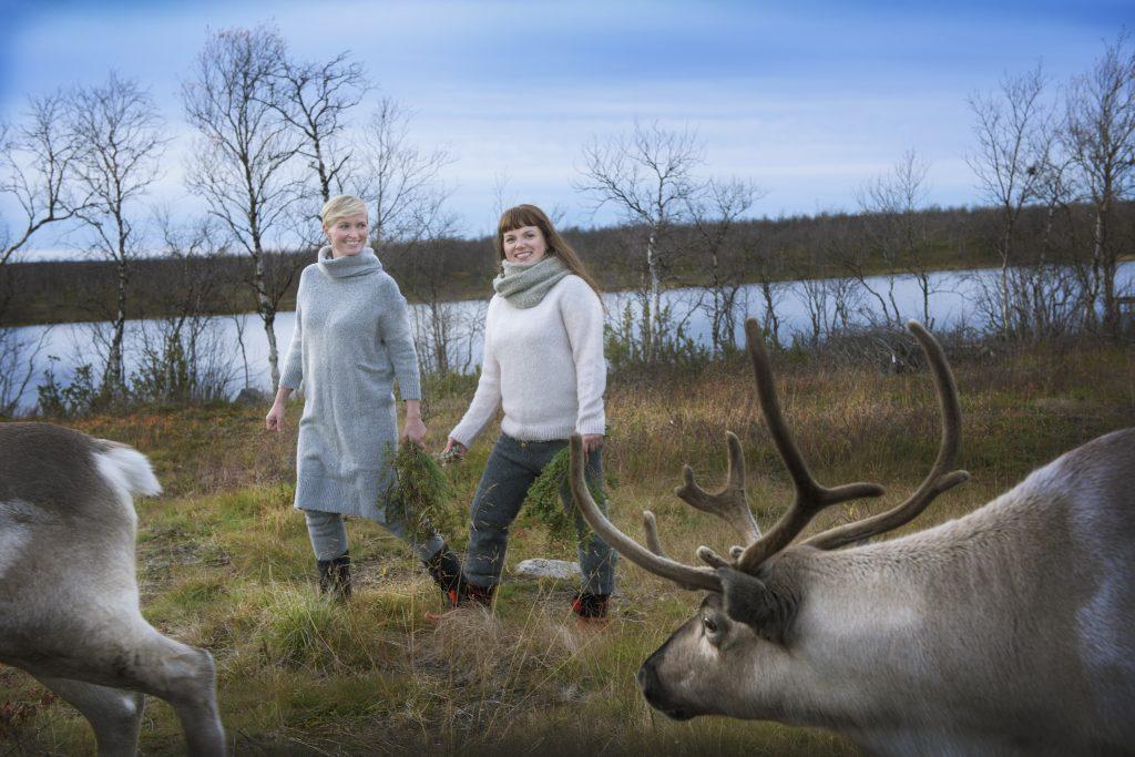 Gründerne bak Rein Styrke Gry og Ellen går sammen med rein i høstlandskap. Innsjø i bakgrunnen og rein i forgrunnen.